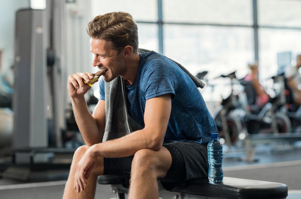 Man Eating Energy Bar in the Gym