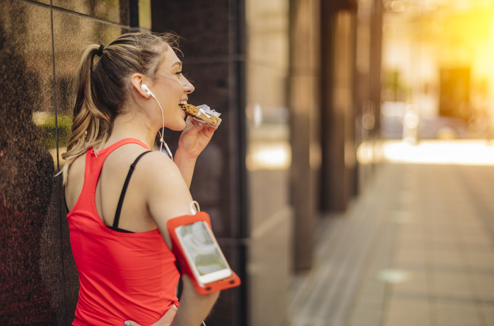 Healthy Snacking - Woman Eating Power Bar